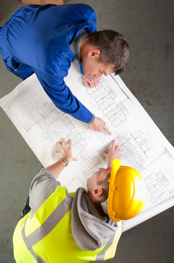 Free Builders Talk About Blueprint On Bench Royalty Free Stock Photography - 16608257