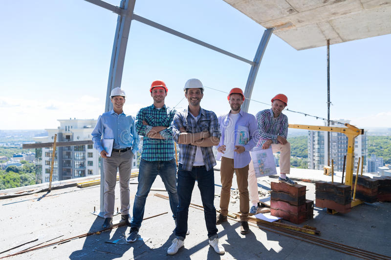 Builders Team Leader With Group Of Apprentices At Construction Site Over City View Background, Happy Smiling Engineers stock photography