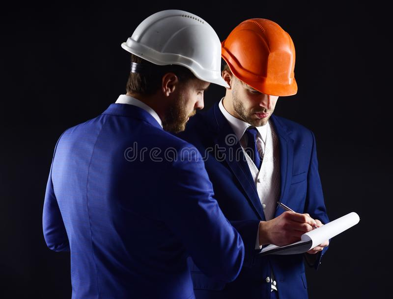 Builders think about engineering project. stock photos