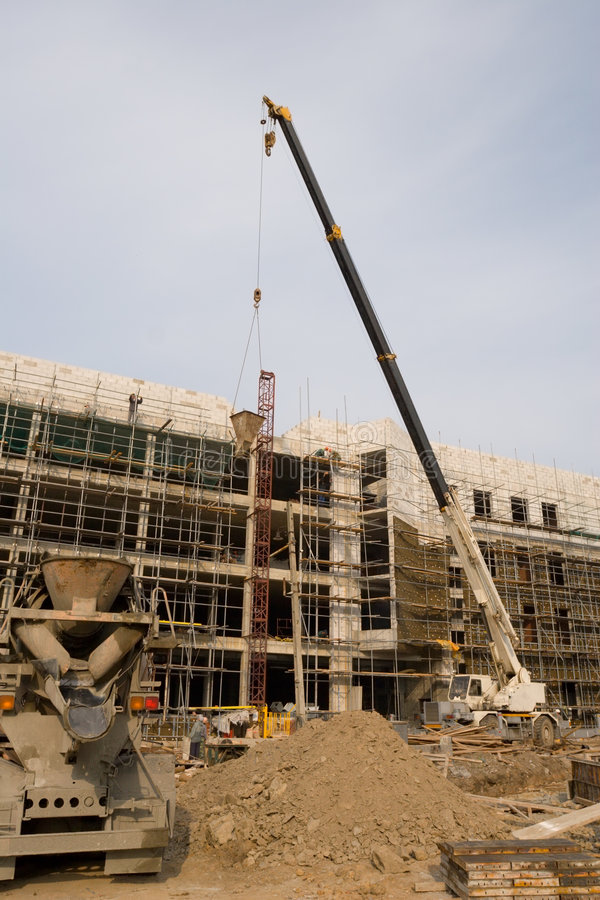 Building. On construction of a new building builders and technics(technical equipment stock photos