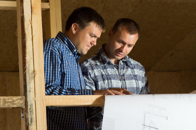 Building Architects Looking at Blueprint Seriously royalty free stock photography