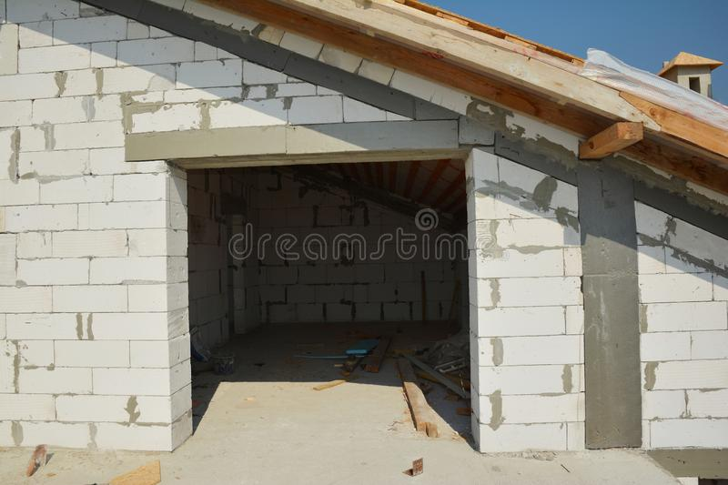 Building Attic Construction from aerated concrete blocks, eathqueke safety reinforcement and wooden roof. Outdoors royalty free stock photography