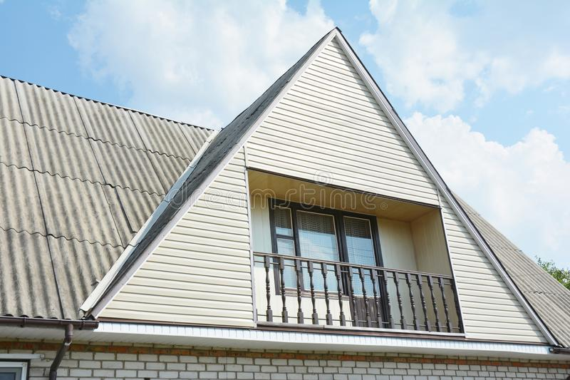 Building attic house construction with asbestos roof, cozy balcony and siding facade royalty free stock photo