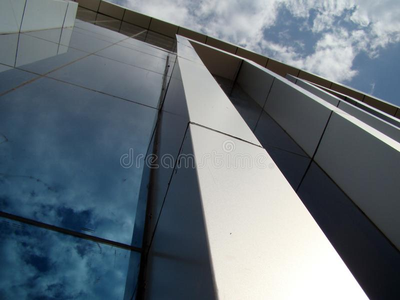 Building on a background of blue sky and clouds with reflection in glasses. royalty free stock image
