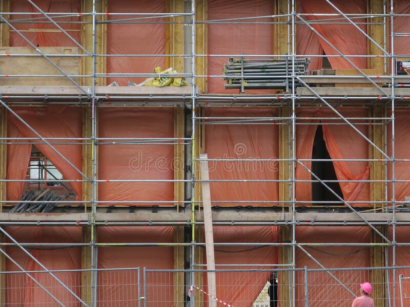 Building being renovated covered with orange colored plastic and scaffolds stock images