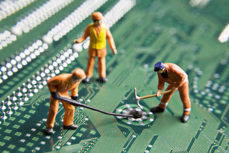 Building a better future. Worker figurines placed on a computer circuit board