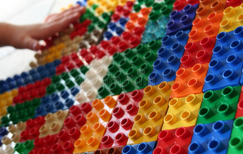 Building blocks 2. Hands of a child building blocks, lining them up in rows. Useful for a building concept or exploring concepts stock image