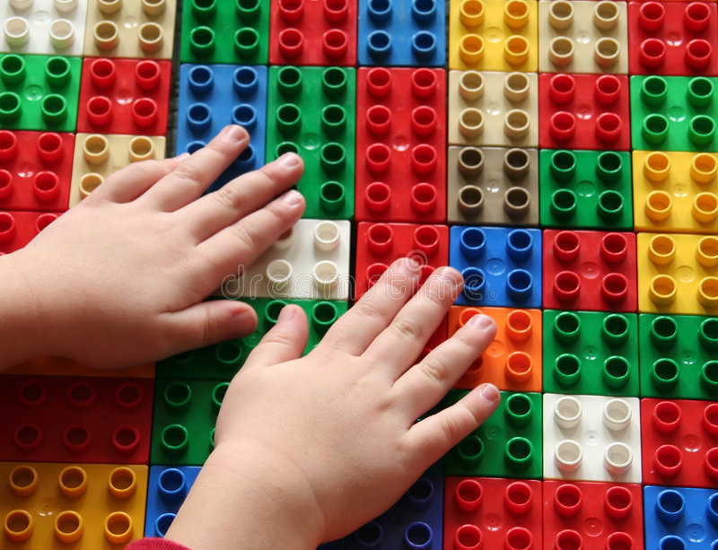 Building blocks 3. Hands of a child building blocks, lining them up in a row. Useful for a building concept or exploring concepts royalty free stock image