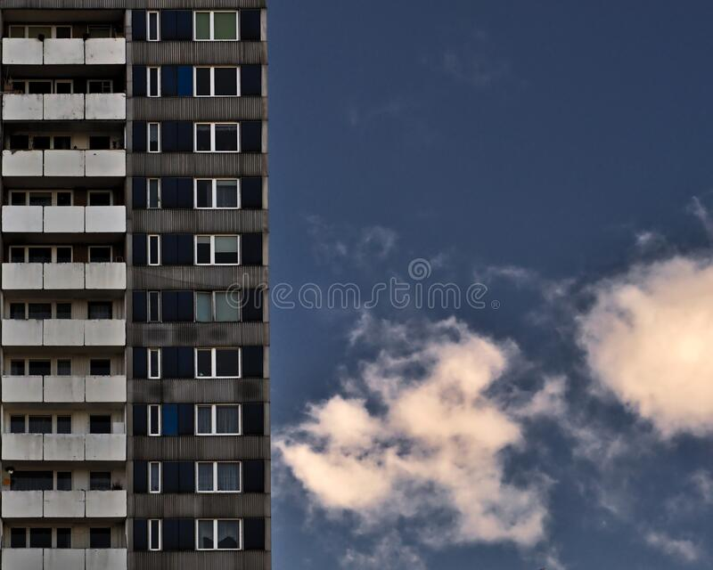 Building and blue sky. Sky with a few clouds. High building with a lot of windows. Building is front. In the background is blue sky with a few clouds stock photos