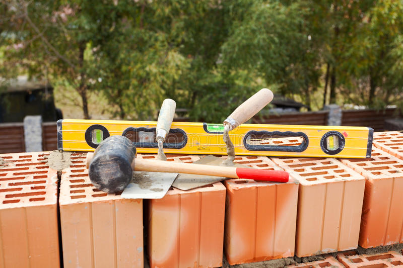 Building a brick wall. Bricklaying instrument spatula, construction level and industrial hammer. Building a brick wall. Bricklaying instrument spatula stock photo