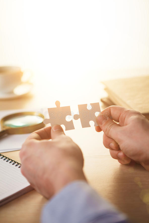 Building a business success. The hands with puzzles stock photos