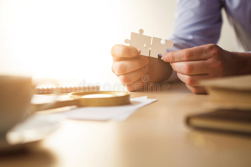 Building a business success. The hands with puzzles royalty free stock images