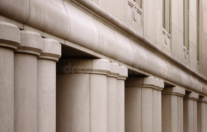 Building with Columns. Architectural details of a large city bank. Focusing on the front of the building, the pillars, and first floor windows stock images