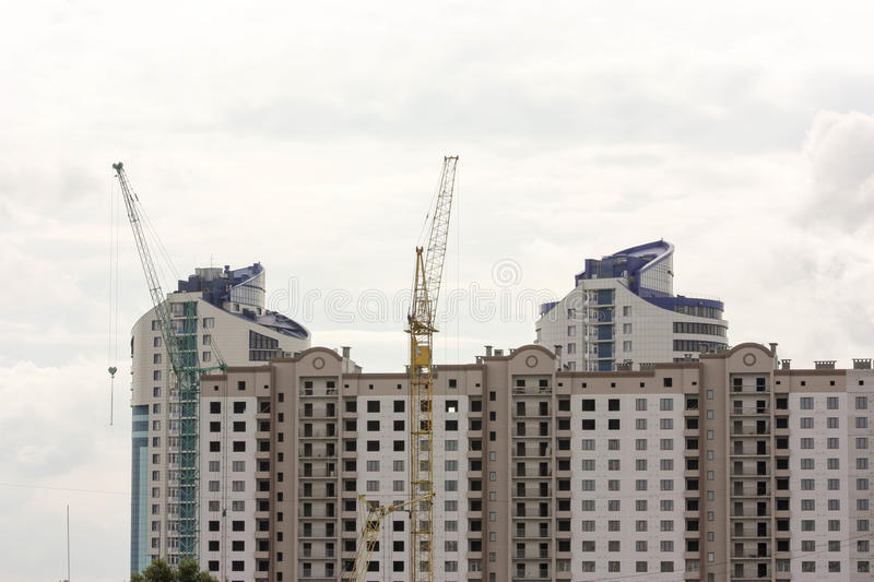 Building concept. Apartment house is a large. And construction crane. Photo horizontal for your design stock images