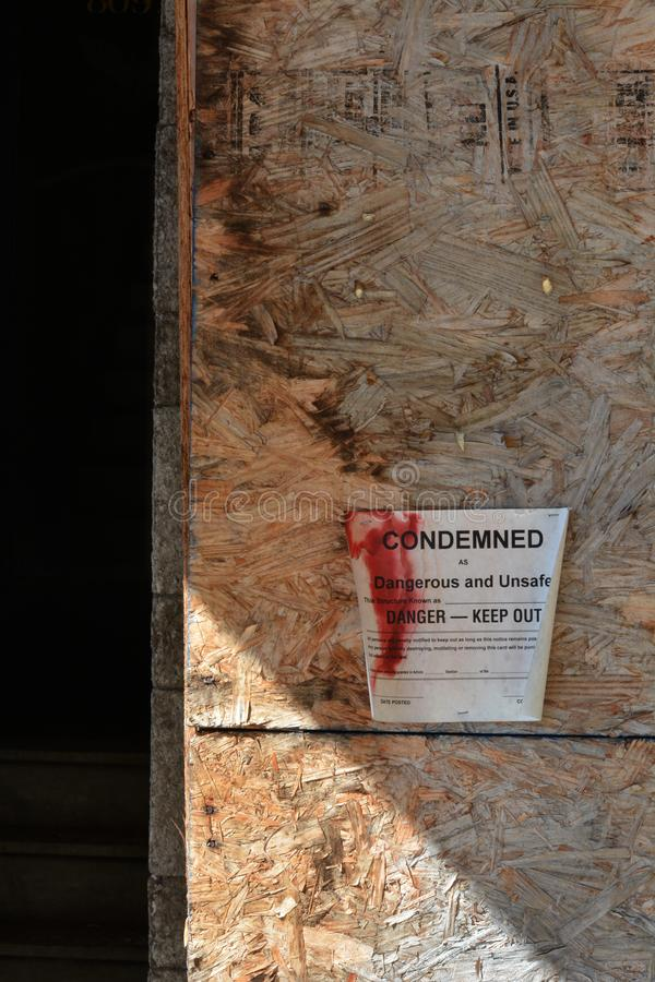 Building condemned. Sign posted on a boarded up window of an old building officially condemning he building for unsafe conditions royalty free stock photo
