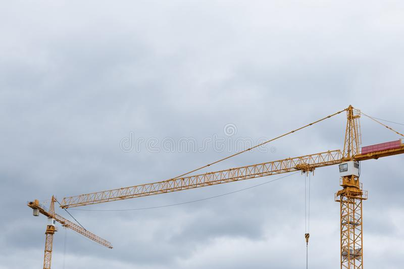 Building constraction cranes against the grey sky. Yellow building constraction cranes against the grey sky stock photography