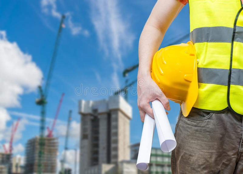 Building construction concept. Worker (engineer) with blueprint. And cranes in background royalty free stock photo