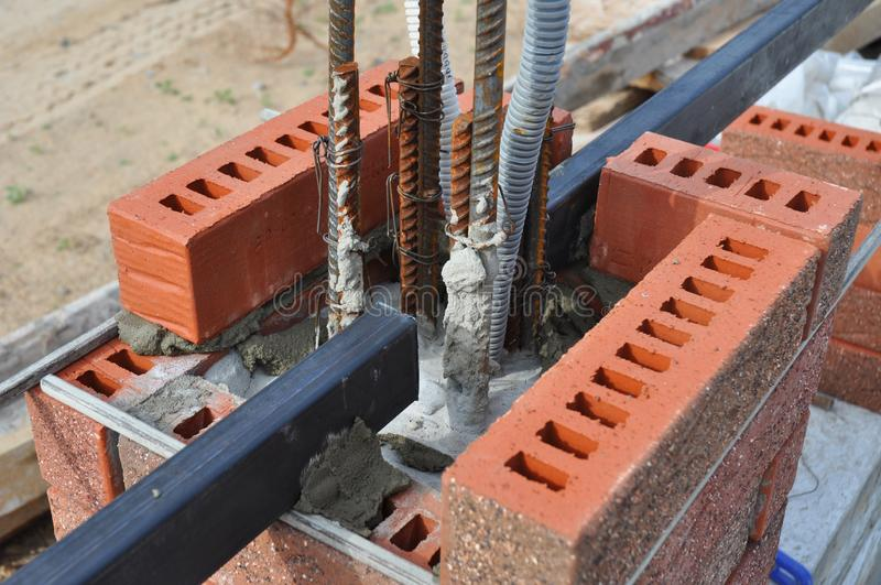 Building construction fence brick column with iron bads, wire for outdoor lighting. Building construction new fence brick column with iron bads, wire for outdoor royalty free stock photography