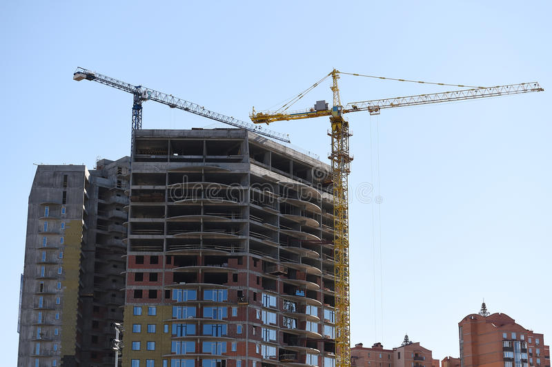 Building construction, lift crane. future and family life, sweet home. Construction of new building with lift crane. real estate. residential house, skyscraper royalty free stock photos