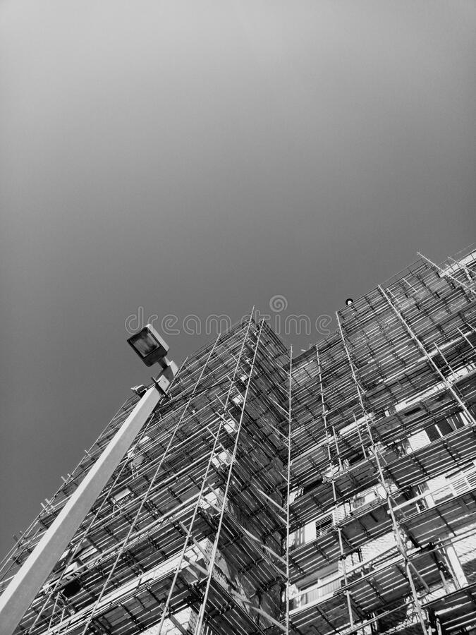 Building in construction site. High angle view of unfinished tall building and high electricity pylon in city royalty free stock photo