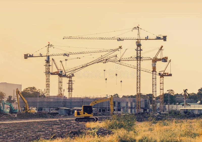 Building construction site with tower crane machinery. Building construction site with tower crane and backhoe machinery in sunset vintage tone color royalty free stock photo