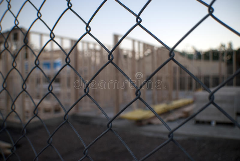 Building construction site through wire fence. Close up of a wire mesh fence with a blurry out of focus construction site in the background royalty free stock photos