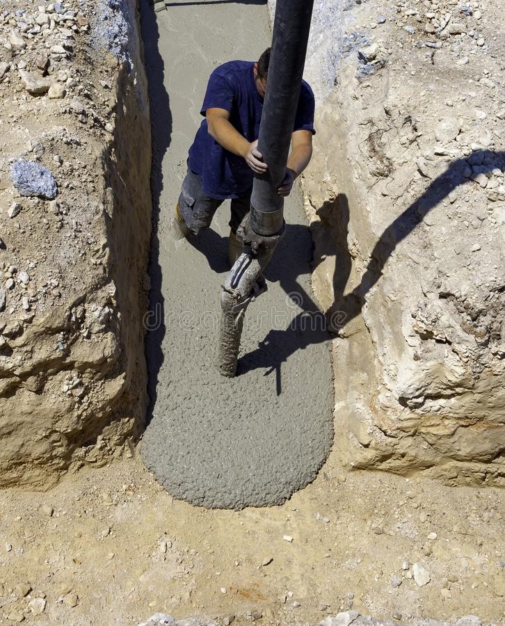 Building construction worker pouring cement royalty free stock image