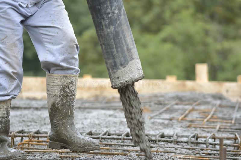 Building construction worker pouring cement stock image
