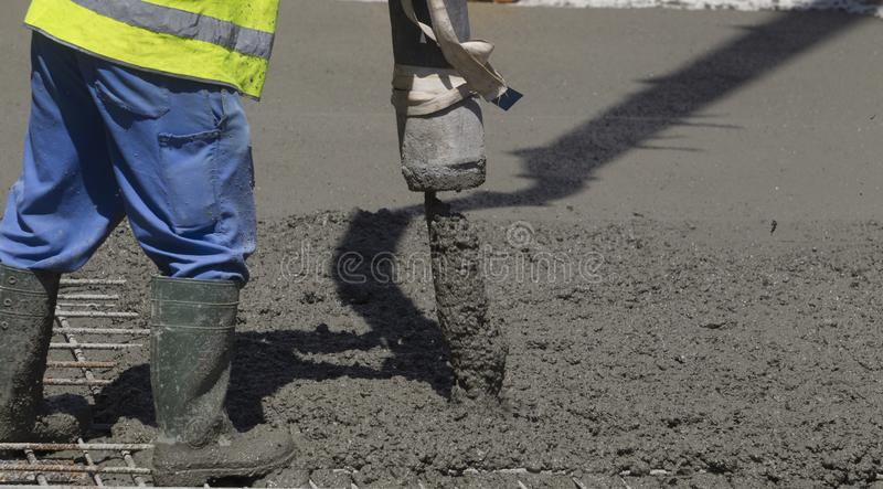 Building construction worker pouring cement or concrete with pump tube stock photos