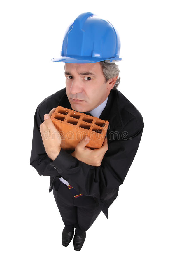 Building contractor with brick. High angle view of middle aged building contractor in safety helmet with brick, isolated on white background stock photos