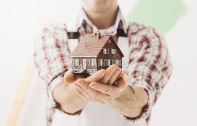 Building your house. Building contractor holding a model house: construction, renovation and real estate concept stock photo