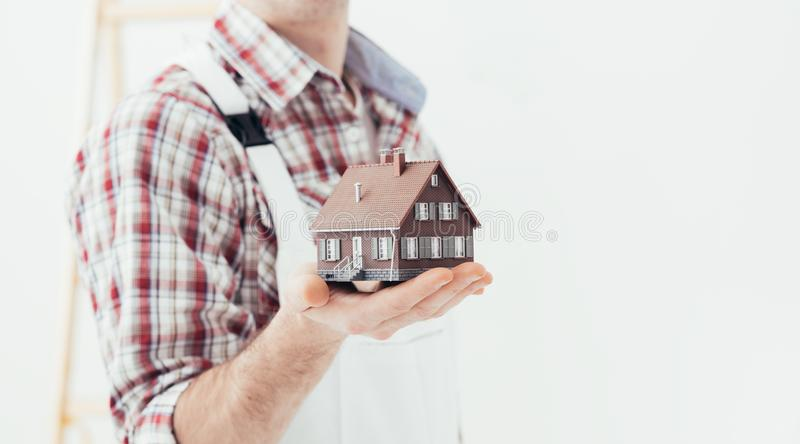 Building your house. Building contractor holding a model house: construction, renovation and real estate concept stock photos