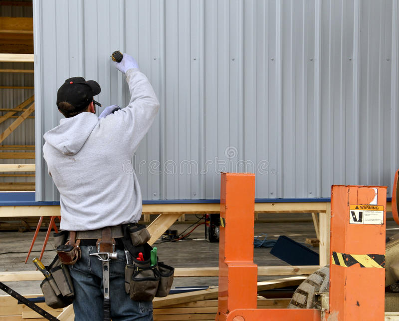 Building contruction worker. Construction worker attaching metal siding to a building stock photo