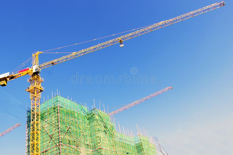 Industrial construction cranes and building silhouettes over sun at sunrise royalty free stock image
