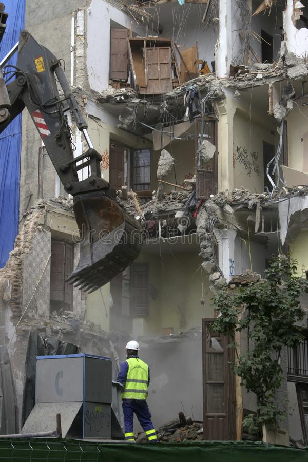 Building demolition, backhoe demolishing a building. Heavy machinery destroying a building stock image