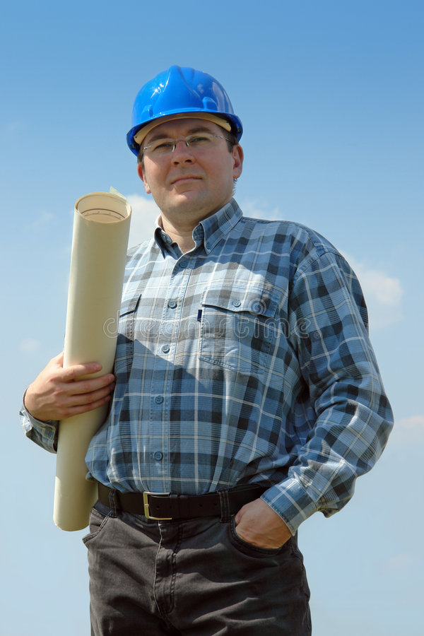 Building designer. Civil engineer wearing blue helmet posing with roll of building plan over blue sky stock photography