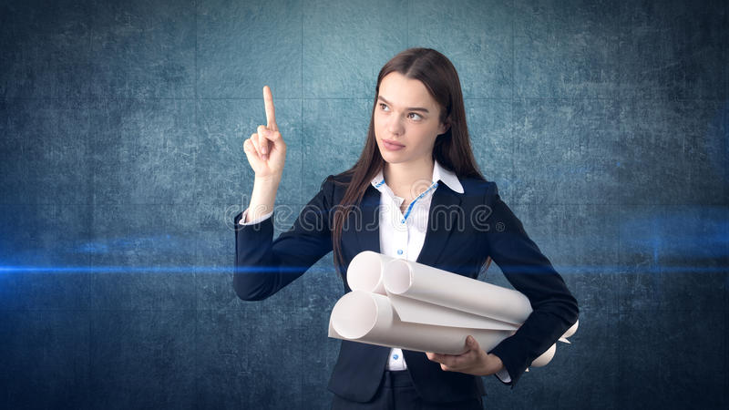 Building, developing, consrtuction and architecture concept - smiling beautiful businesswoman in suit with blueprint stock photos