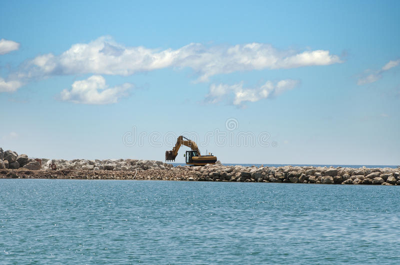 Building a dike. Excavator put stones royalty free stock photo