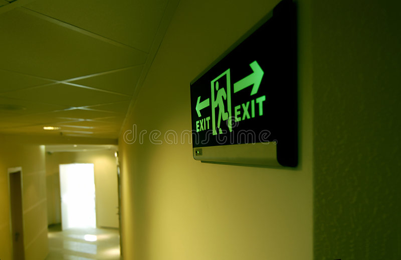 building emergency exit glowing green sign 免版税库存照片