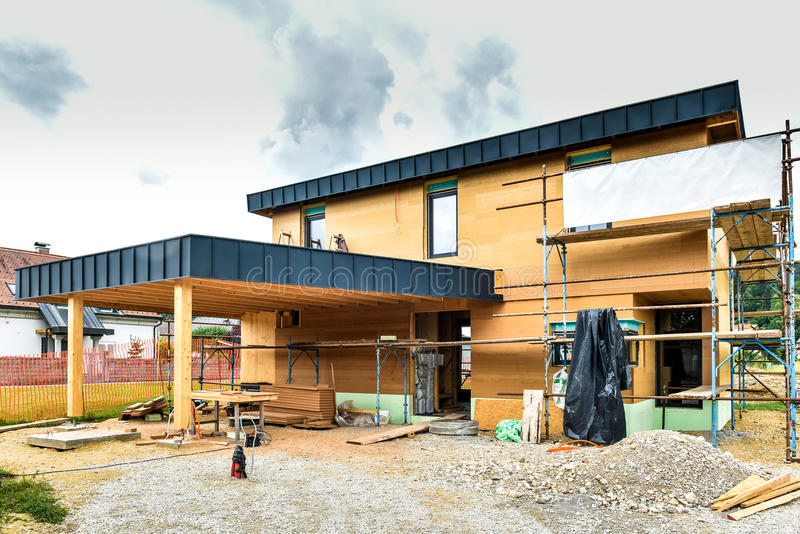 Building energy efficient passive wooden house. Construction site and exterior of a wooden panel house with scaffolds ready for wall insulation stock images