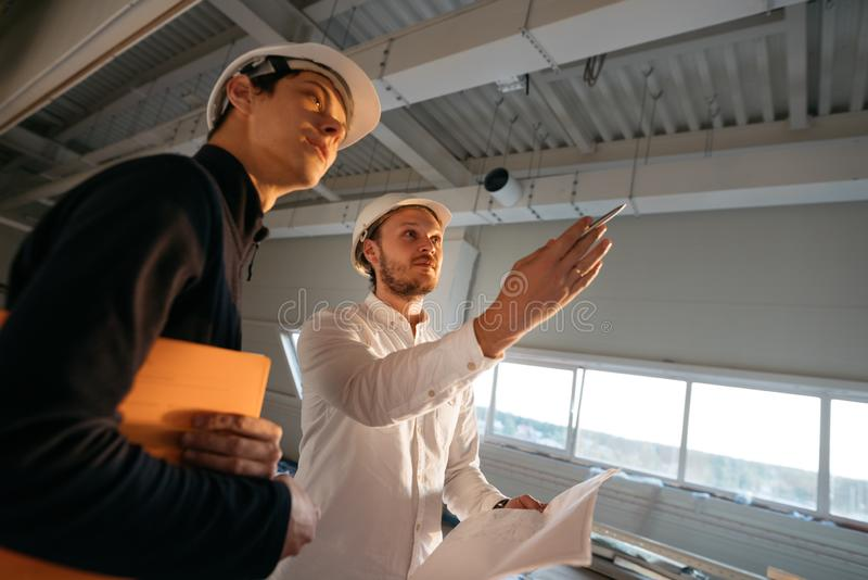 Building engineer and worker hold blueprint in hand while discussong construction site royalty free stock images