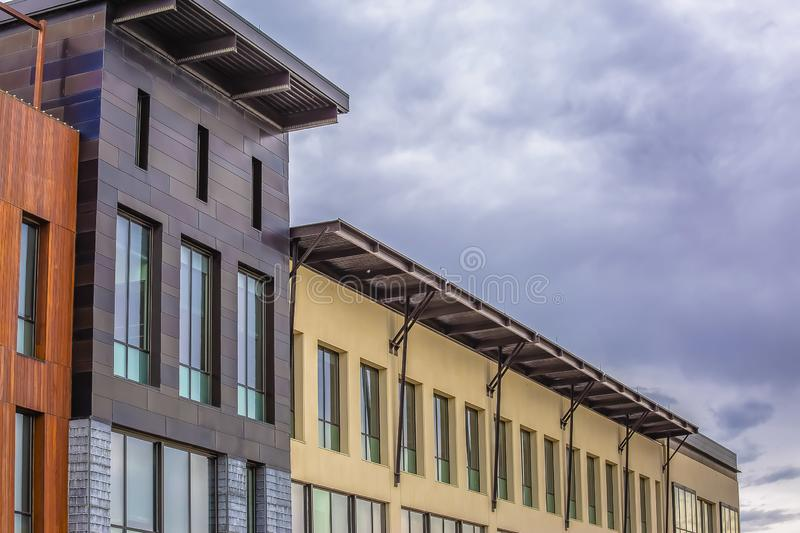 Building exterior with a flat roof against sky covered with puffy gray clouds. The rectangular windows allow light into the rooms and reflect the outdoor stock images