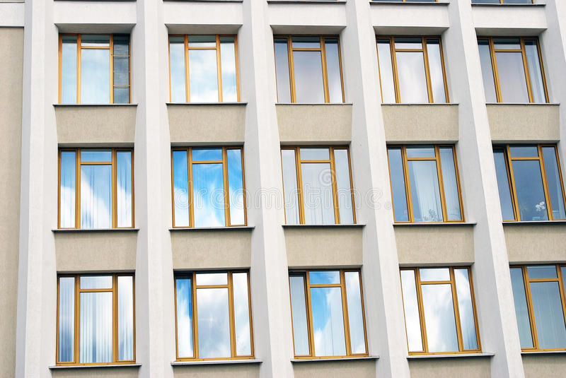 A building facade, glass windows, blue sky reflection. Taken in Russia stock photos