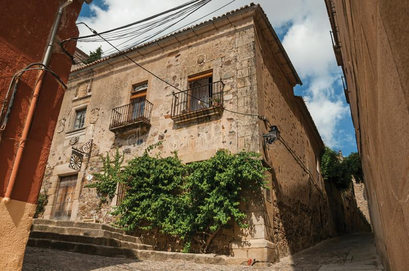 Building facade with green creeper, on corner of narrow alley at Caceres royalty free stock photography