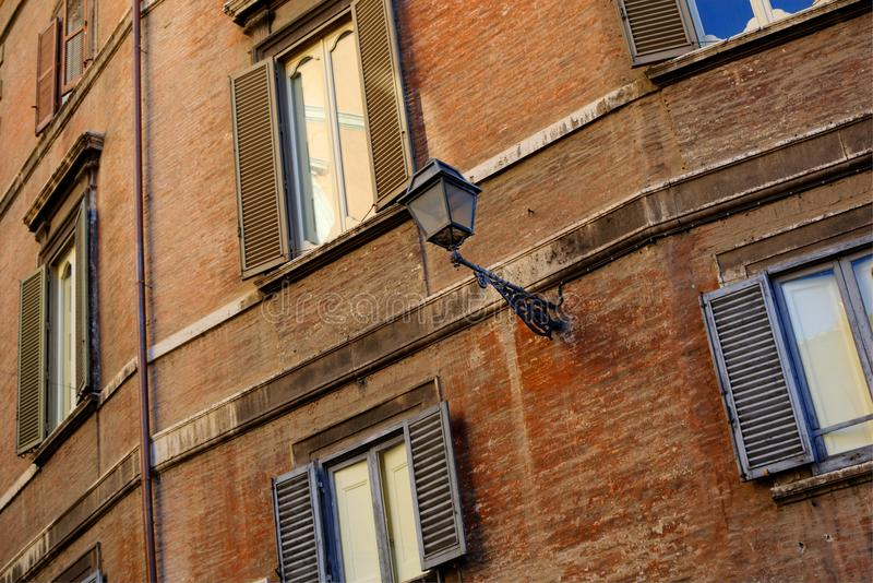 Building Facade, Rome, Italy. Vintage facade of apartment block in Rome, Italy, with windows, blinds and a lamp royalty free stock photo