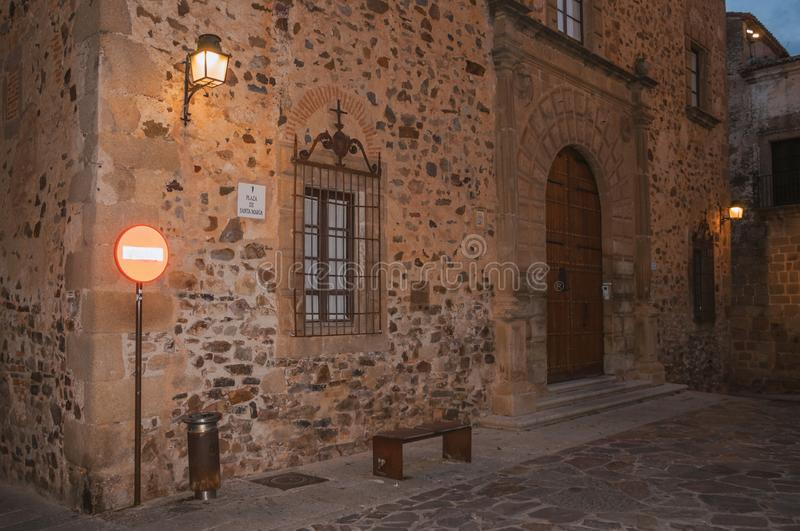Building facade with wooden door and traffic sign. Caceres, Spain - July 02, 2018. Old building facade with wooden door, barred window and traffic sign at dusk stock image