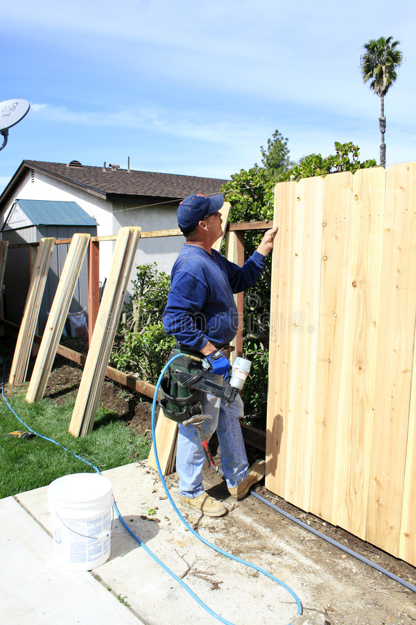 Building a Fence. Men building a Fence in garden stock photos