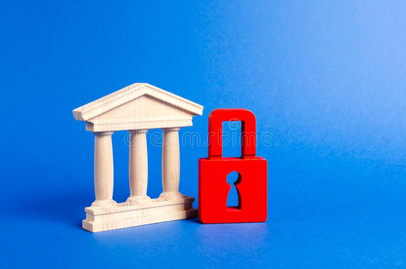 Building figurine with pillars in antique style and red padlock. Ineffective government, seizure of property and liquidation. Of the bank. Saving architectural royalty free stock photography