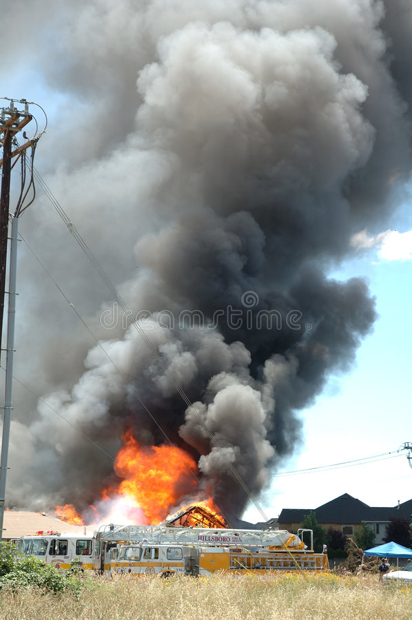 Building on fire. Huge flames and thick columns of black smoke rise in the air as a building burns royalty free stock photo