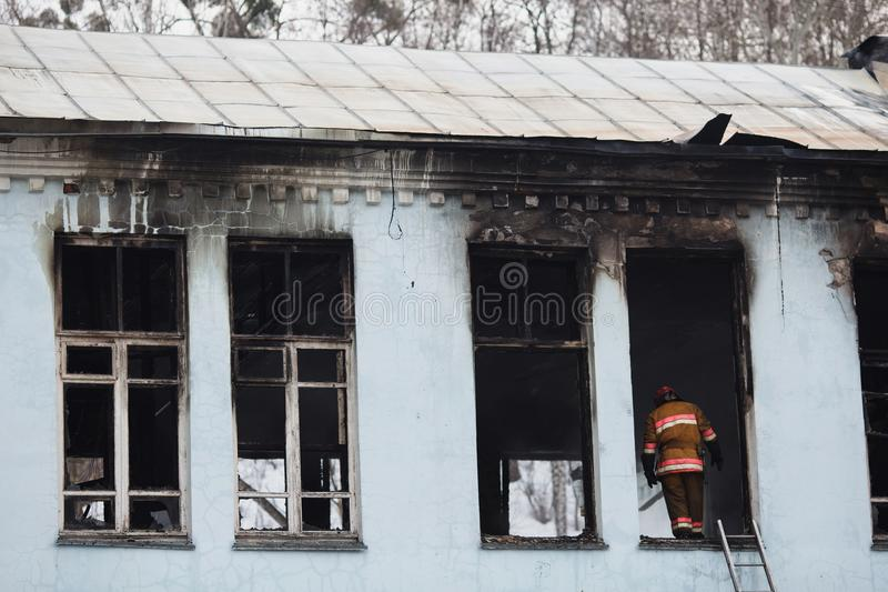 The building after the fire. Burnt window. Rescuers firefighters extinguish a fire on the roof. The building after the fire. Burnt window. Ruined house stock photos